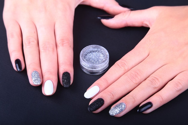 Schwarz-weiße nailart-maniküre. helle maniküre im urlaubsstil mit glitzern. flasche nagellack. schönheit hände. stilvolle nägel, nagellack.