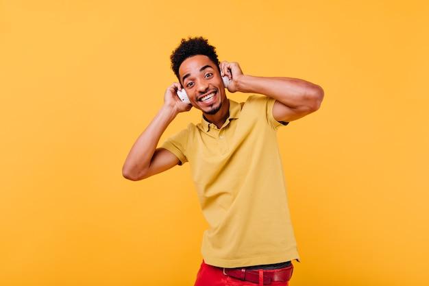 Schwarzäugiger lustiger mann, der seine kopfhörer berührt. erstaunliches afrikanisches modell, das musik hört.