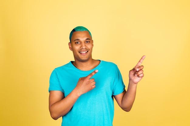 Schwarzafrikaner in lässig auf gelber wand glücklich positiv und zeigefinger nach rechts zeigen