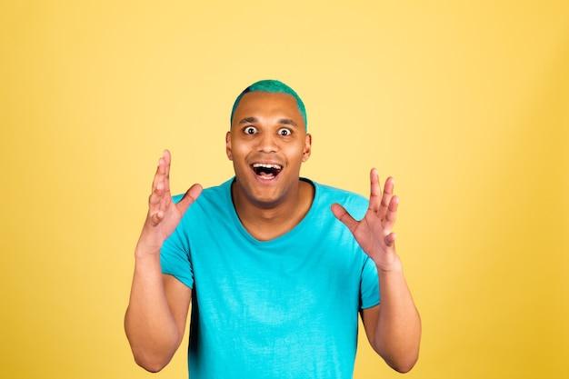 Schwarzafrikaner in lässiger auf gelber wand mit schockiertem erstauntem überraschtem offenem gesicht des mundes