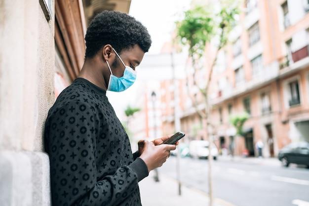 Schwarzafrikaneramerikaner auf der straße mit einer blauen gesichtsmaske, die sein handy betrachtet, das sich vor der covid-19-coronavirus-pandemie schützt