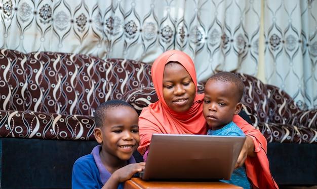 Schwarzafrikanische familie, die hauptschule mit digitalem laptop während der quarantänezeit tut