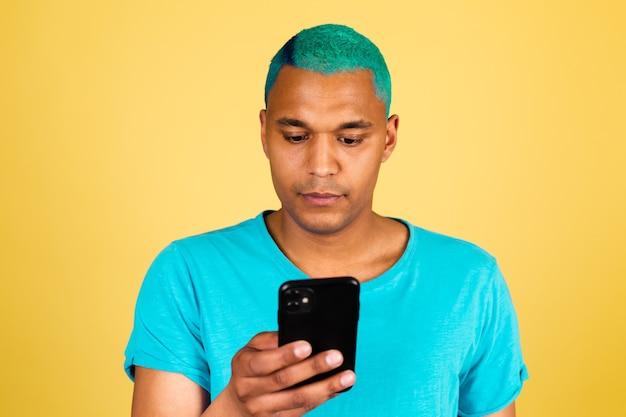 Schwarzafrikanischer mann in lässig auf gelber wand mit handy ernstem gesichtsblick auf bildschirm lesen nachrichten