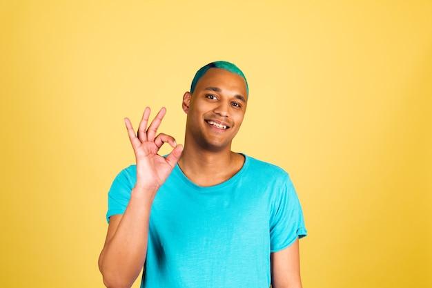 Schwarzafrikanischer mann in lässiger auf gelber wand glücklicher blick zur kamera mit lächeln zeigen ok geste