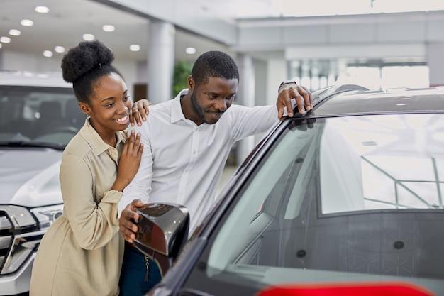 Schwarzafrikanisches paar mochte ein auto im autohaus
