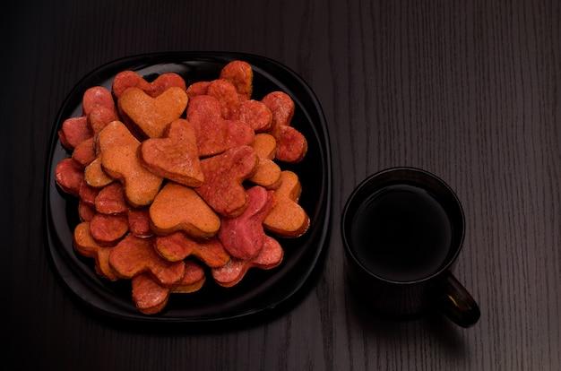 Schwarzblech mit roten herzförmigen plätzchen und einer tasse tee auf einer schwarzen tabelle, valentinstag. ansicht von oben