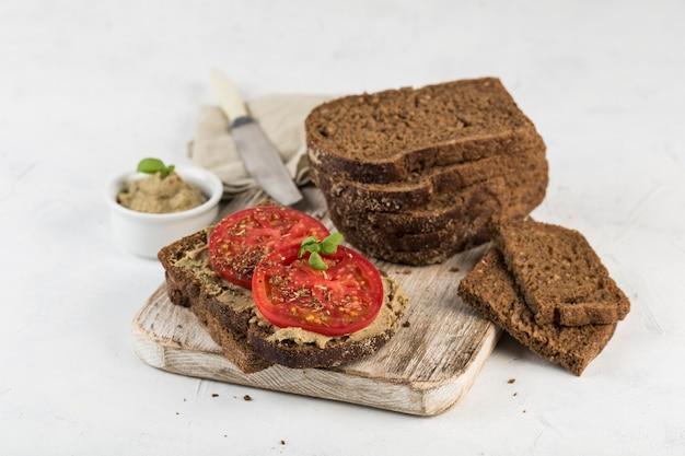 Schwarzbrot-sandwich mit tomaten und hummus auf einem holzbrett