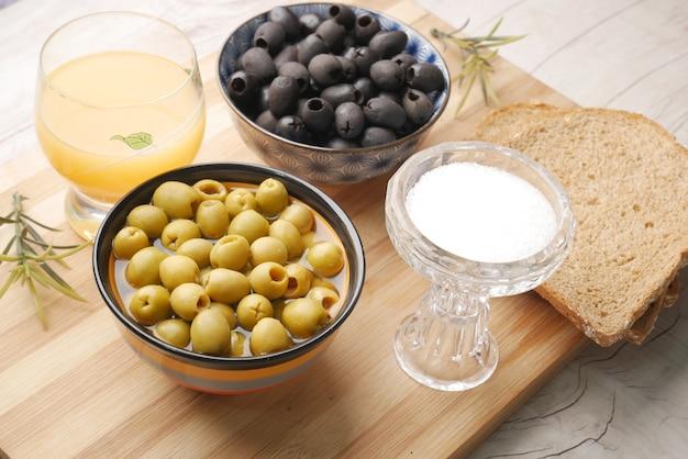 Schwarzbrotsaft frische grüne schwarze olive in einem behälter auf dem tisch