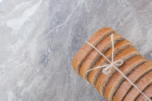Schwarzbrotscheiben im seil auf marmoroberfläche