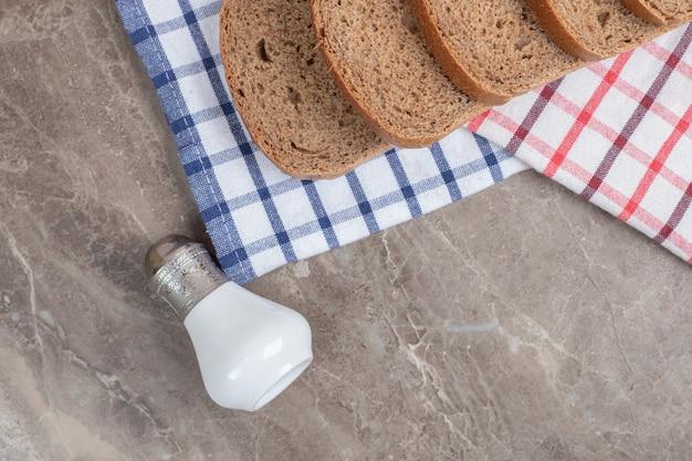 Schwarzbrotscheiben und salz auf tischdecken. hochwertiges foto