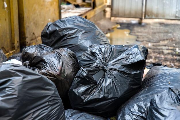 Schwarze abfalltaschen und unscharfer schmutziger nasser bodenhintergrund