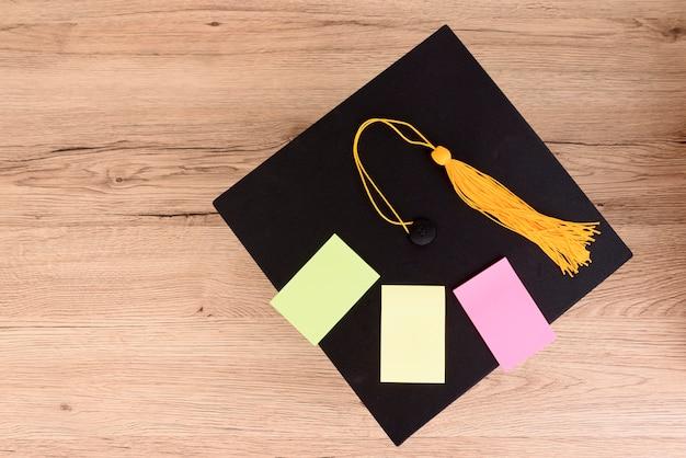 Schwarze abgestufte kappe und gelbe quaste auf holztisch, buntes papierpost-it-tempo auf kappe