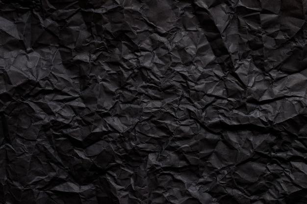 Schwarze abstrakte hintergrundtextur durch dunkles zerknittertes papier