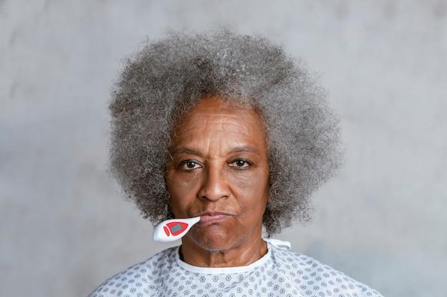 Schwarze ältere patientin, die ihre temperatur überprüft