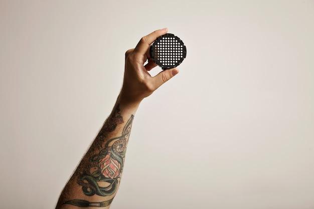 Schwarze aeropress-filterkappe, die von einer tätowierten männerhand, die auf weiß isoliert ist, in der luft gehalten wird