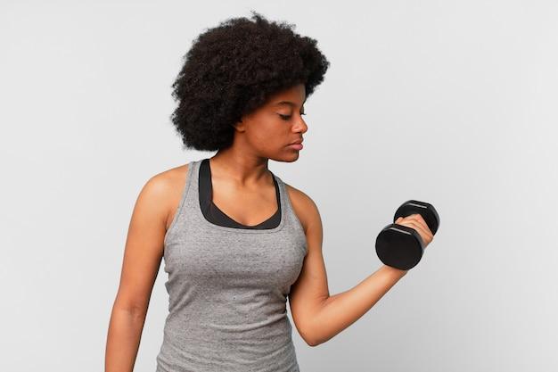 Schwarze afro-fitness-frau mit hantel