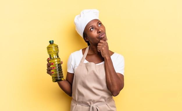 Schwarze afro-kochfrau, die denkt, sich zweifelnd und verwirrt fühlt, mit verschiedenen optionen und sich fragt, welche entscheidung sie treffen soll. olivenöl konzept