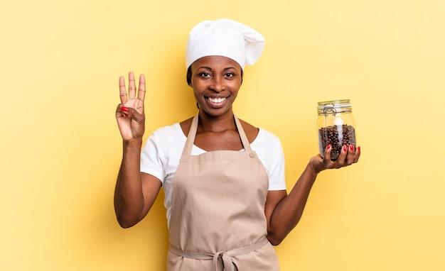 Schwarze afro-kochfrau, die lächelt und freundlich aussieht, nummer drei oder dritte mit der hand nach vorne zeigend, herunterzählen. kaffeebohnen-konzept