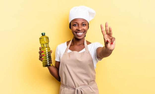 Schwarze afro-kochfrau, die lächelt und freundlich aussieht, nummer drei oder dritte mit der hand nach vorne zeigend, herunterzählen. olivenöl konzept
