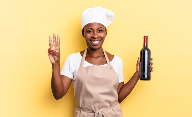 Schwarze afro-kochfrau, die lächelt und freundlich aussieht, nummer drei oder dritte mit der hand nach vorne zeigend, herunterzählen. weinflaschenkonzept