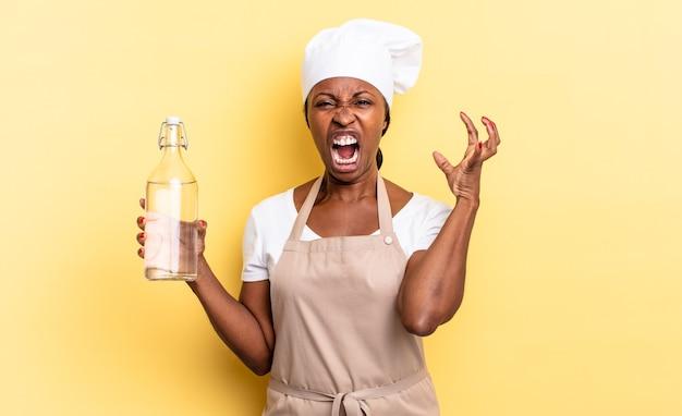 Schwarze afro-kochfrau, die mit den händen in der luft schreit, sich wütend, frustriert, gestresst und verärgert fühlt, wenn sie eine wasserflasche hält