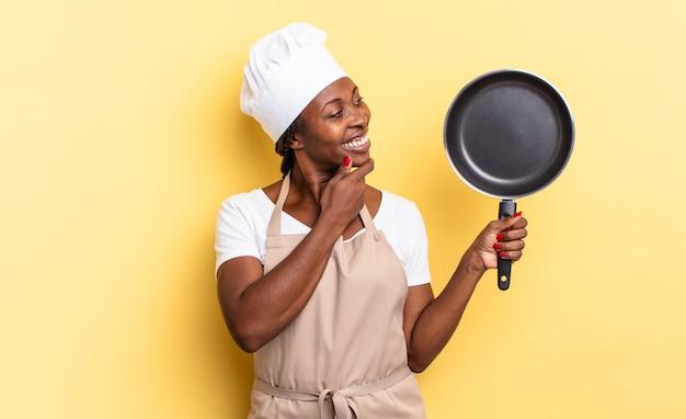 Schwarze afro-kochfrau, die mit einem glücklichen, selbstbewussten ausdruck mit der hand am kinn lächelt, sich wundert und zur seite schaut