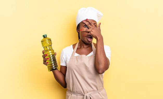 Schwarze afro-kochfrau, die schockiert, verängstigt oder verängstigt aussieht, das gesicht mit der hand bedeckt und zwischen den fingern späht. olivenöl konzept