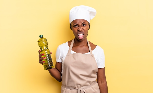 Schwarze afro-kochfrau, die sich angewidert und irritiert fühlt, die zunge herausstreckt und etwas böses und ekelhaftes nicht mag. olivenöl konzept