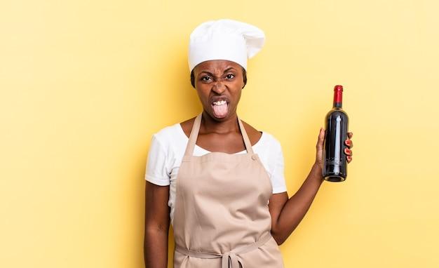 Schwarze afro-kochfrau, die sich angewidert und irritiert fühlt, die zunge herausstreckt und etwas böses und ekelhaftes nicht mag. weinflaschenkonzept