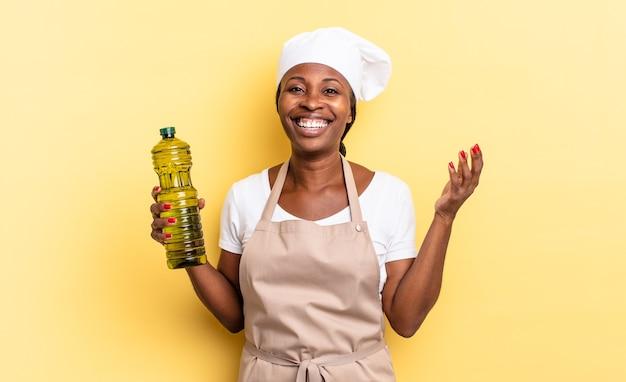 Schwarze afro-kochfrau, die sich glücklich, überrascht und fröhlich fühlt, mit positiver einstellung lächelt und eine lösung oder idee realisiert. olivenöl konzept