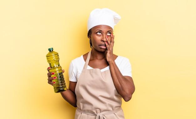 Schwarze afro-kochfrau, die sich nach einer ermüdenden, langweiligen und mühsamen aufgabe gelangweilt, frustriert und schläfrig fühlt und das gesicht mit der hand hält. olivenöl konzept