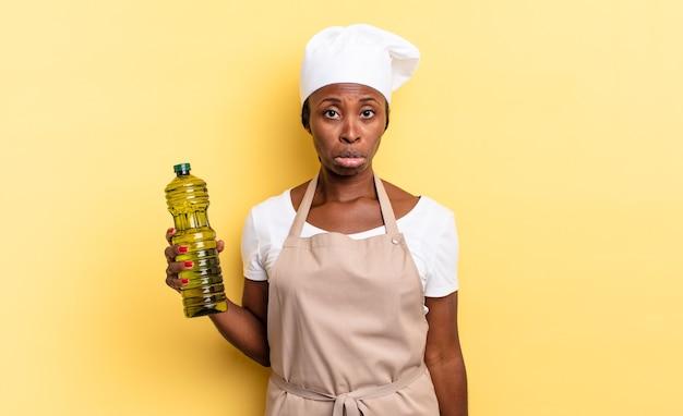 Schwarze afro-kochfrau, die sich traurig und weinerlich mit einem unglücklichen blick fühlt und mit einer negativen und frustrierten haltung weint. olivenöl konzept