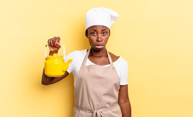 Schwarze afro-kochfrau, die sich traurig und weinerlich mit einem unglücklichen blick fühlt und mit einer negativen und frustrierten haltung weint. teekanne konzept