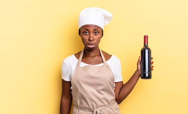 Schwarze afro-kochfrau, die sich traurig und weinerlich mit einem unglücklichen blick fühlt und mit einer negativen und frustrierten haltung weint. weinflaschenkonzept
