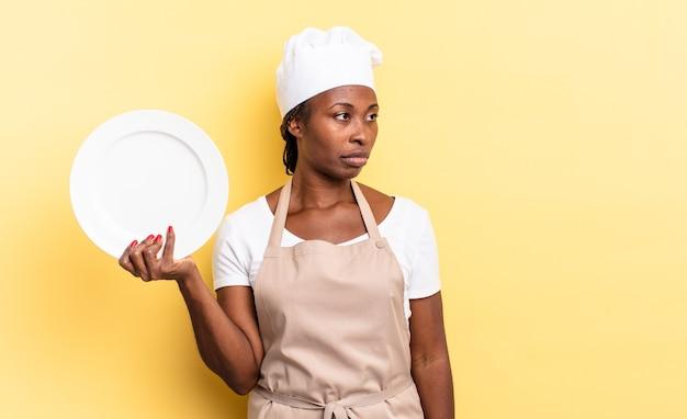 Schwarze afro-kochfrau, die sich traurig, verärgert oder wütend fühlt und mit einer negativen einstellung zur seite schaut und die stirn runzelt. leerplattenkonzept