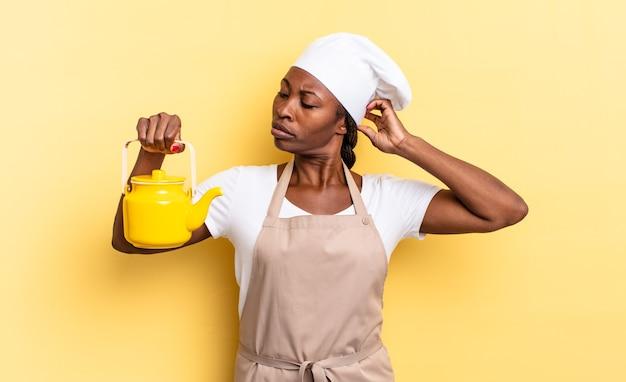 Schwarze afro-kochfrau, die sich verwirrt und verwirrt fühlt, den kopf kratzt und zur seite schaut. teekannenkonzept