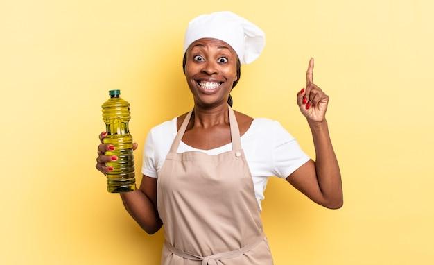 Schwarze afro-kochfrau, die sich wie ein glückliches und aufgeregtes genie fühlt, nachdem sie eine idee verwirklicht hat, fröhlich den finger hebt, heureka!. olivenöl konzept