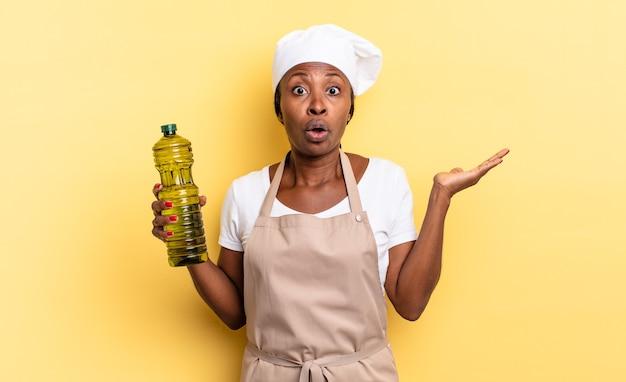 Schwarze afro-kochfrau, die überrascht und schockiert aussieht, mit heruntergefallenem kiefer, die einen gegenstand mit offener hand an der seite hält. olivenöl konzept