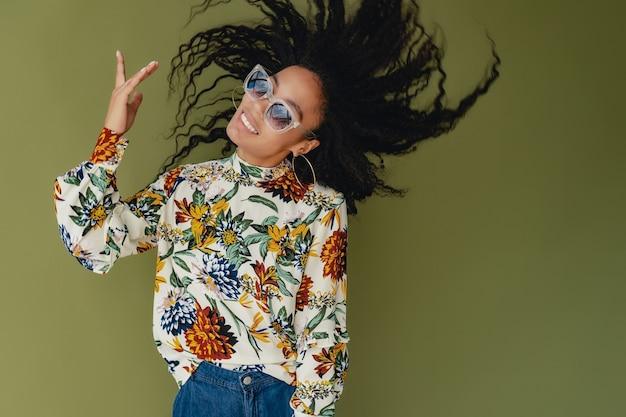 Schwarze afroamerikanerin in stylischen outfit-jeans und bluse isoliert auf grün