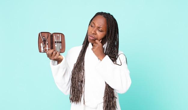 Schwarze afroamerikanische erwachsene frau, die bademantel trägt und eine make-up-tasche mit nains-tools hält