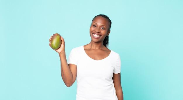 Schwarze afroamerikanische erwachsene frau, die eine mangofrucht hält