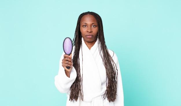 Schwarze afroamerikanische erwachsene frau, die einen bademantel trägt und eine haarbürste hält Premium Fotos