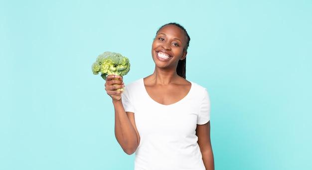 Schwarze afroamerikanische erwachsene frau, die einen brokkoli hält