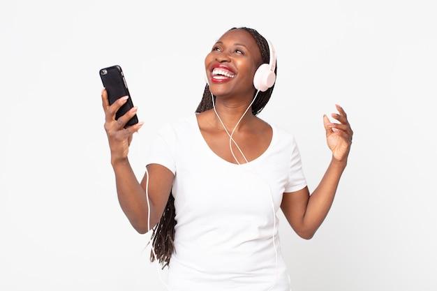 Schwarze afroamerikanische erwachsene frau, die musik mit kopfhörern und smartphone hört