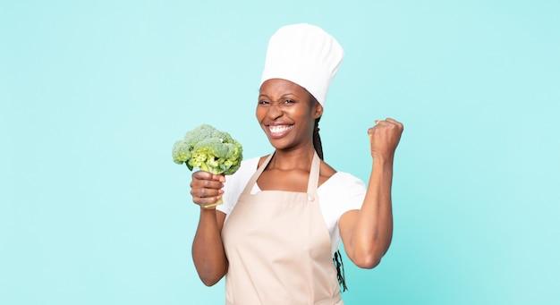 Schwarze afroamerikanische erwachsene kochfrau, die einen brokkoli hält
