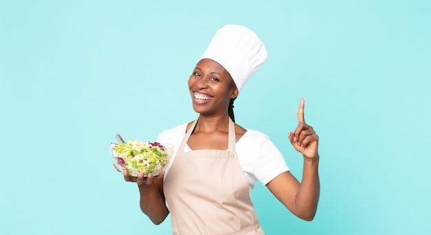 Schwarze afroamerikanische erwachsene kochfrau, die einen salat hält
