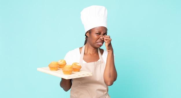Schwarze afroamerikanische erwachsene kochfrau mit einem muffins-tablett
