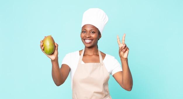 Schwarze afroamerikanische erwachsene kochfrau mit einer mango