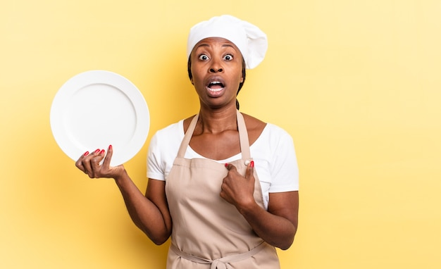 Schwarze afrokochfrau, die schockiert und überrascht mit weit geöffnetem mund aussieht und auf sich selbst zeigt. leerplattenkonzept