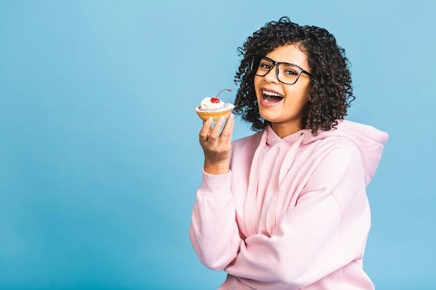 Schwarze amerikanische afrikanische glückliche frau mit lockiger afro-frisur, die ein durcheinander macht, das ein großes ausgefallenes dessert über blauem hintergrund isst. cupcake essen.